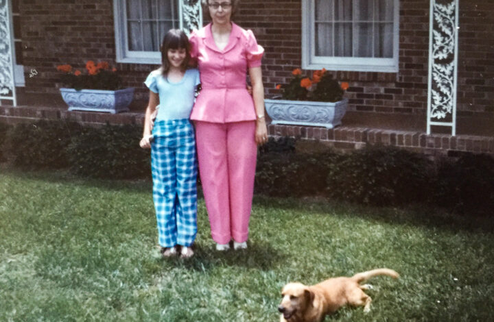 Woman and girl with brown dog on lawn