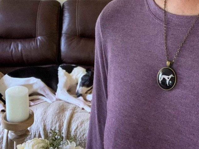 Woman wearing whippet pendant necklace with whippet on couch behind her.