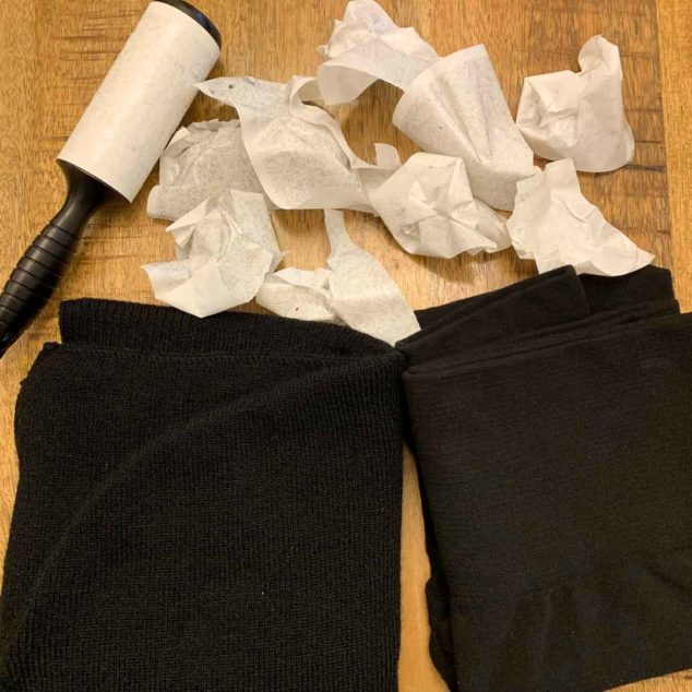 Lint roller and used roller sheets next to black scarf and leggings.