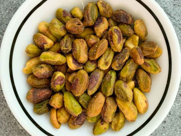 shelled and roasted pistachio nuts in a small white bowl.
