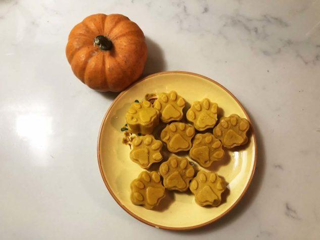 Pumpkin spice dog treats on a yellow plate next to a small pumpkin