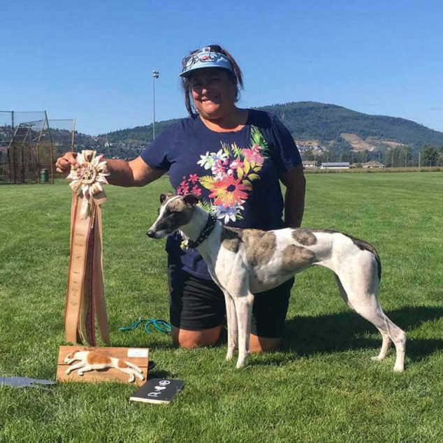 Woman holding a winner ribbon next to a whippet