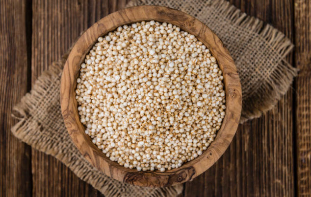 raw uncooked quinoa in a wood bowl