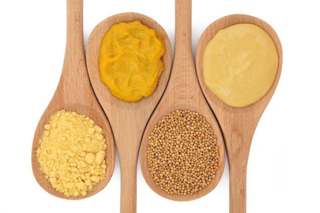 mustard powder, yellow mustard, mustard seeds, and dijon mustard in wooden spoons