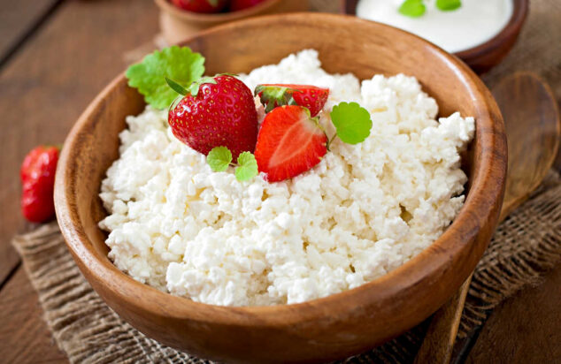 a bowl of cottage cheese topped with strawberries