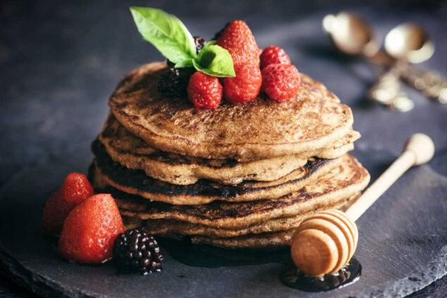 a stack of buckwheat pancakes with berries and honey