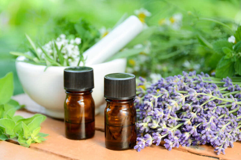 two essential oil bottles and fresh herbs