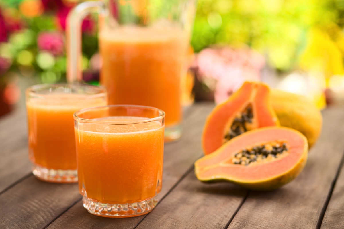 two glasses of papaya juice and fresh papaya fruit