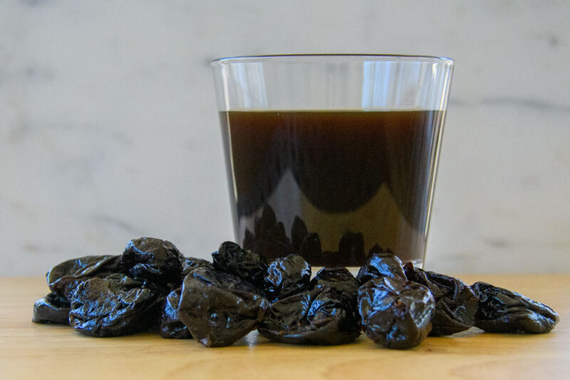 prune juice in a glass and prunes