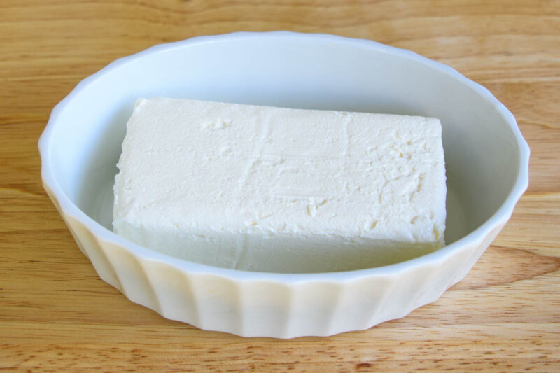 a block of cream cheese in a dish