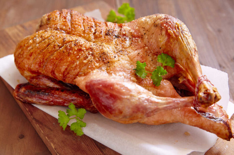 whole roasted duck on a cutting board