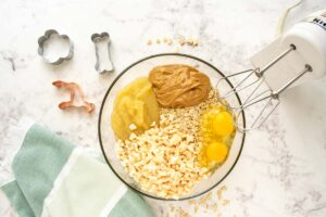 combining ingredients for apple oatmeal dog treats in a bowl