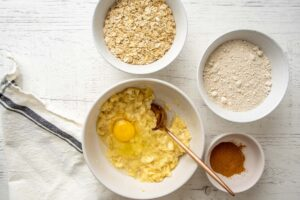 egg and mashed bananas in a bowl, rolled oats, oat flour, and cinnamon