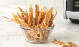 a bowl of homemade chicken jerky treats for dogs next to a dehydrator