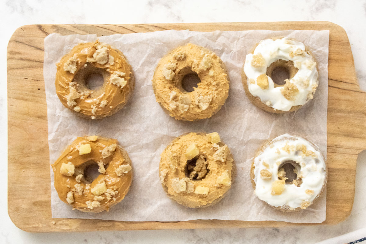 six homemade dog donuts with icing on parchment paper