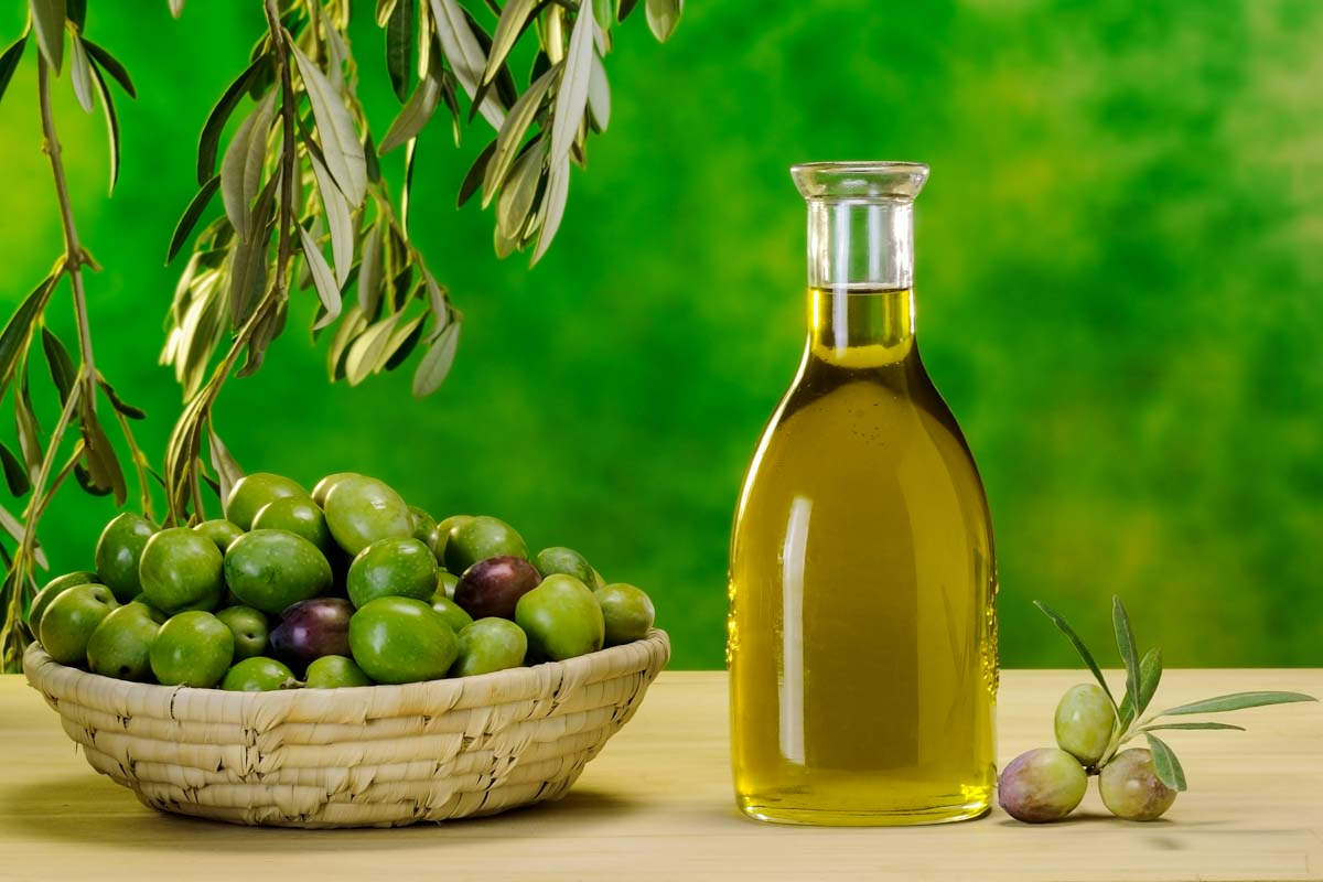 a bowl of olives and a container of olive oil