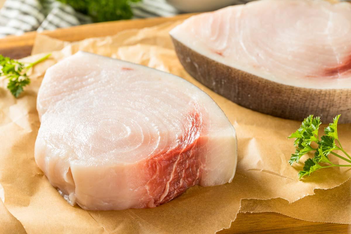 two swordfish steaks on parchment paper