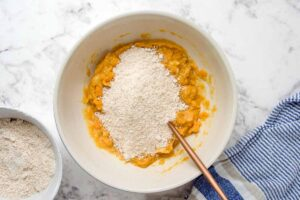 oat flour and wet ingredients for sweet potato dog treats in a bowl.