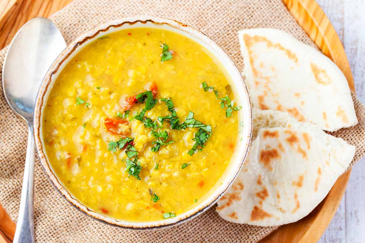 a bowl of yellow lentil dal soup and pita bread slices