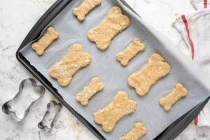 apple dog treats dough cutouts on a baking sheet.